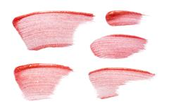 Different lip glosses isolated on white. Smudged lip gloss sample. Stock Photos