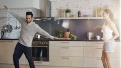 Happy Couple Creatively Dances in the Kitchen. Both are Adorable and Smiling. Stock Footage
