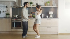 Happy Young Couple Dances in the Kitchen ending up in a Embrace. Stock Footage