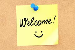 Welcome text on a sticky note pinned to a corkboard. 3D rendering Stock Illustration