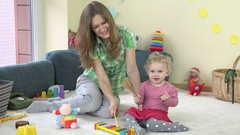 Toddler girl playing instruments like metallophone and rattle with babysitter Stock Footage