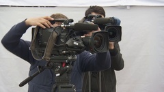 Two cameramans in the city shoot video the news in the city among people Stock Footage