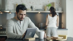 On the Kitchen Young Man Drinks From a Cup while Using Tablet.  Stock Footage