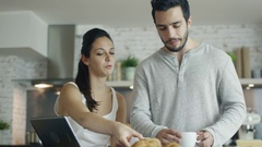 Handsome Couple in the Kitchen with Tablet on the Table. She eats Croissant. Stock Footage