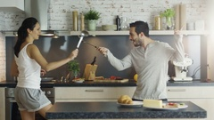 On the Kitchen Young Handsome Couple is Fencing with Kitchen Appliances.  Stock Footage