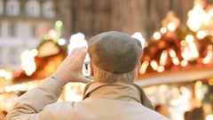 Christmas Market Atmosphere senior man taking view pictures smartphone Stock Footage