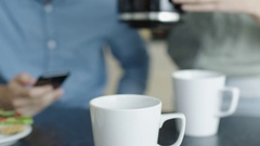 Close-up of a Woman Pouring Coffee from Coffee Pot for Two. Stock Footage