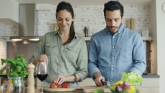 Young Couple Prepares Food on the Kitchen. They are Cutting Vegetables and Talk. Stock Footage