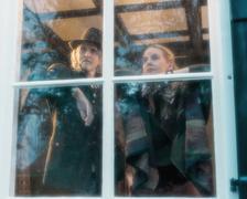 Pensive vintage 1970s musicians standing behind rainy window looking outside. Kuvituskuvat
