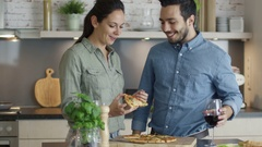 In the Kitchen Young Woman Gives Her Boyfriend Bite of Her Pizza Slice. Stock Footage