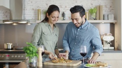 In the Kitchen Young Couple Hungrily and Smilingly Taste Pizza. Stock Footage