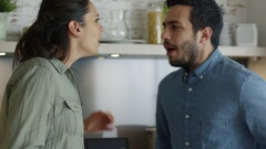 Young Couple Quarrels in the Kitchen. Man and Woman Scream. Stock Footage