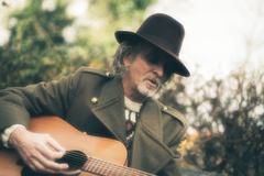 Vintage guitarist performing in autumn garden. Stock Photos