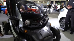 Visitors of auto show examine new mini electric city car RENAULT ZE TWIZY. Stock Footage