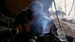 Phrehistoric cave man makes first fire, blows on it in his cave on the Stock Footage