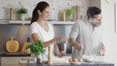 Happy Young Couple Cooks in the Kitchet. As a Joke They Started Throwing Flour. Stock Footage