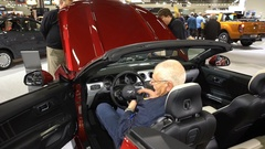 Stand of new models Mustang at the auto show. Visitors examine interior of new v Stock Footage