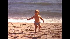 Vintage 16mm film, 1946, California, toddler walking at beach, proud dad Stock Footage