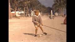 Vintage 16mm film, 1946, California, toddler and boy raking sand play Stock Footage