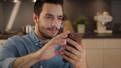 Handsome Young Man Smilingly Uses Smartphone in the Kitchen. Stock Footage