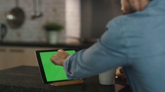In the Kitchen. Young Man Sips From a Cup While Using  Tablet Computer. Stock Footage