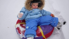 A happy child rides in snowtube on a snow Stock Footage