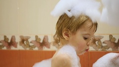 Child having fun playing with foam in the bath Stock Footage