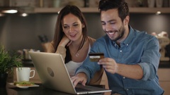 Happy Couple Uses Laptop for Internet Purchases, Handsome Man Has Credit Card. Stock Footage