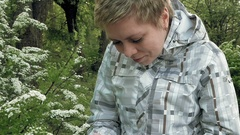 Pretty blond girl looks at flowers in a green park Stock Footage