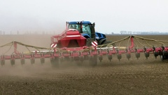 Tractor ploughs tills plows and seeds on the field Stock Footage