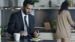 Handsome Businessman Uses Tablet Computer while Having Breakfast at His Kitchen  Stock Footage