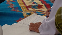 Man Writes in Wedding Register Book on Carpet Stock Footage