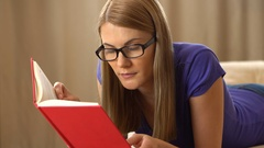 Beautiful attractive young woman in a violet t-shirt and a black glasses lying Stock Footage