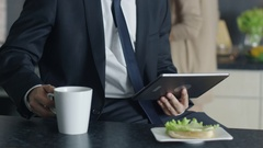 Close-up of a Handsome Businessman Using Tablet Computer while Having Breakfast  Arkistovideo