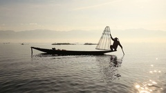 Burmese fisherman on boat catching fish in Inle lake, Myanmar, Burma Stock Footage
