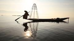Burmese fisherman on boat catching fish in Inle lake, Myanmar, Burma Stock Footage