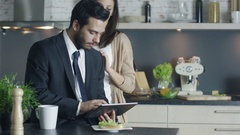 Handsome Businessman Sits at His Kitchen Using Tablet Computer. Stock Footage