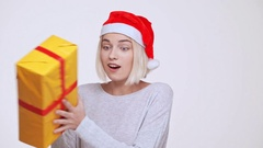 Young beautiful blonde girl in christmas hat suddenly getting gift box White Stock Footage