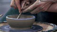 Potters hands guiding hand the student to work correctly on the potter's wheel Stock Footage