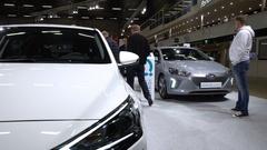 Visitors examine new cars Hyundai IONIQ Electric and Hyundai IONIQ Hybrid. Stock Footage