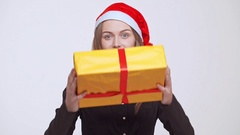 Young beautiful excited fair-haired girl in christmas hat giving gift box over Stock Footage