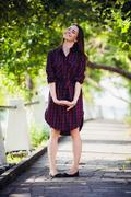 Beautiful, pretty woman in casual checkered dress walking at park outdoors Stock Photos