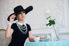 Woman in hat, much like the famous actress, croissant eating and drinking tea Stock Photos