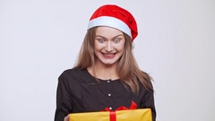 Young beautiful excited fair-haired girl in christmas hat holding gift box Stock Footage