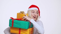 Young pretty blonde girl in christmas hat hardly holding stack of falling gift Stock Footage