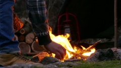 4K.Bonfire with man tourist body. Put firewood in  fire Stock Footage