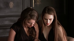 Beautiful girls in elegant dresses leaf journal and discussing Christmas Stock Footage