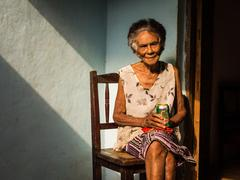 Old Cuban woman on chair enjoying a beer Stock Photos