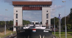 Inland cargo ship slowly enters lock chamber of Eefde lock complex Stock Footage