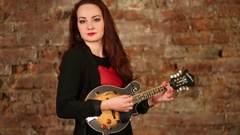 Woman playing on eight string electrical ukulele near brick wall. Stock Footage